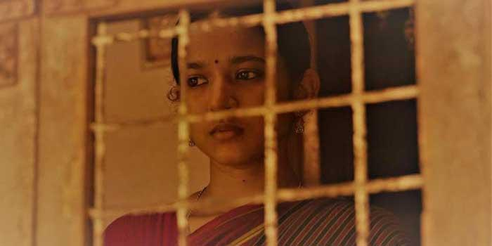 Garggi Ananthan as Kalyani, standing by the window